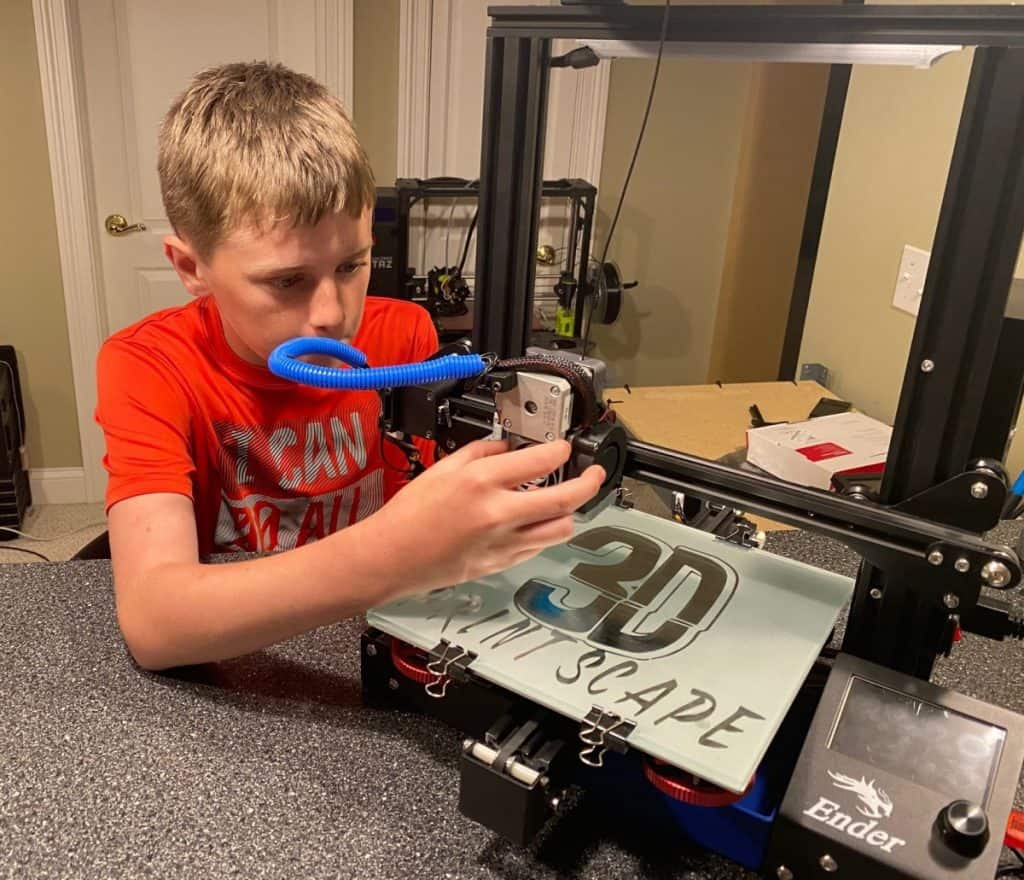 Kid working on 3d printer close up